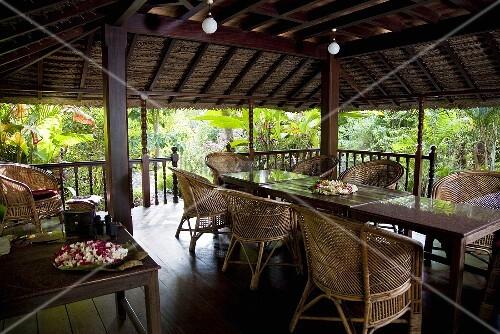 berdachter terrassenplatz mit korbm bel und kugelleuchten in tropischer umgebung bild kaufen. Black Bedroom Furniture Sets. Home Design Ideas