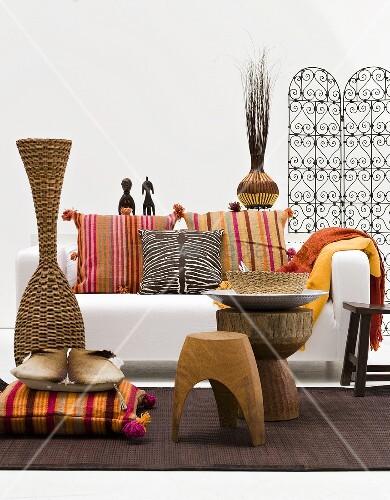 kissen vor bodenvase aus rattan und rustikale hocker vor weissem sofa mit bunten kissen bild. Black Bedroom Furniture Sets. Home Design Ideas