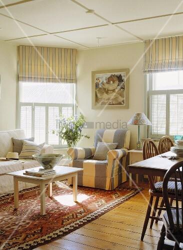 wohnzimmer mit meeresblick mit dielenboden und teppich mit blau weiss gestreiftem sessel und. Black Bedroom Furniture Sets. Home Design Ideas