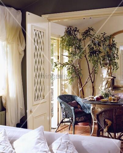 blick auf ein esszimmer mit runder tisch und korbsessel. Black Bedroom Furniture Sets. Home Design Ideas