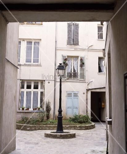 alte strassenlaterne im innenhof eines hauses in paris. Black Bedroom Furniture Sets. Home Design Ideas