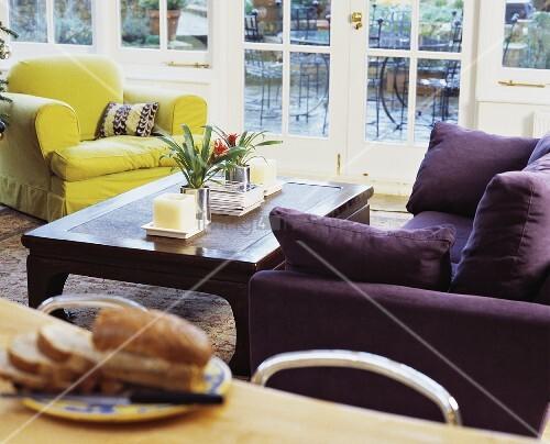 violettes polstersofa und gelber sessel mit ethno. Black Bedroom Furniture Sets. Home Design Ideas
