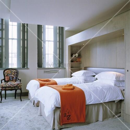 orangefarbene tagesdecke auf getrennt stehenden betten und fenster mit innenseitigen l den. Black Bedroom Furniture Sets. Home Design Ideas