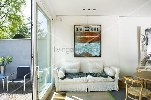 weisses polstersofa an wand und terrassenfenster mit offener t r und blick auf terrasse bild. Black Bedroom Furniture Sets. Home Design Ideas