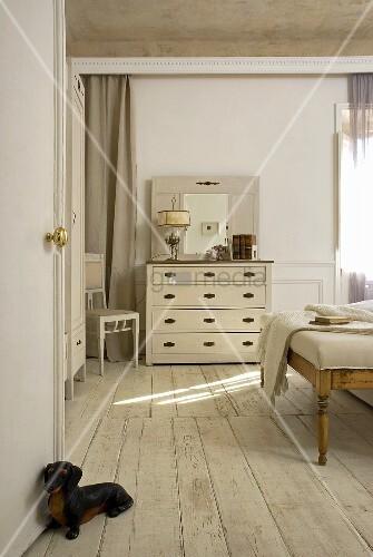 blick durch offene t r mit tierfigur als t rstopper auf weiss lackierten dielenboden und kommode. Black Bedroom Furniture Sets. Home Design Ideas