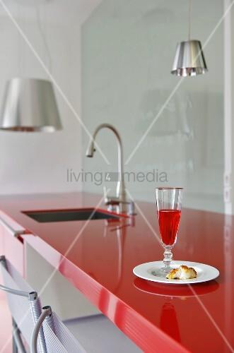 glas mit rotem getränk auf roter küchenarbeitsplatte – bild kaufen