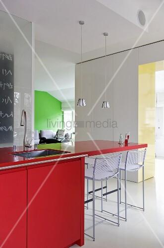 roter k chenblock mit auskragender platte und barhocker in moderner k che bild kaufen. Black Bedroom Furniture Sets. Home Design Ideas