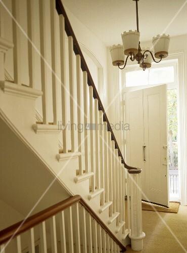 Offene haustür  Treppe mit Geländer aus Holz in weissem Flur und offene Haustür ...