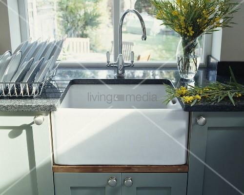 einbauwaschbecken mit granit arbeitsplatte und vase mit gelben mimosen vor fenster bild kaufen. Black Bedroom Furniture Sets. Home Design Ideas