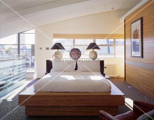 offener designer schlafraum unter dach mit matratze im holzrahmen vor trennwand im gleichen holz. Black Bedroom Furniture Sets. Home Design Ideas
