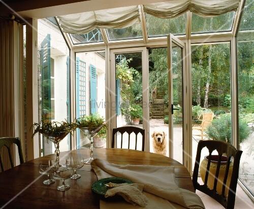 essplatz in wintergarten mit ausblick auf garten mit hund und blaue fensterl den des. Black Bedroom Furniture Sets. Home Design Ideas