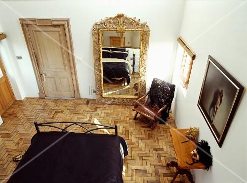 blick von oben auf schlafzimmer im stilmix mit vergoldetem spiegel auf parkett bild kaufen. Black Bedroom Furniture Sets. Home Design Ideas
