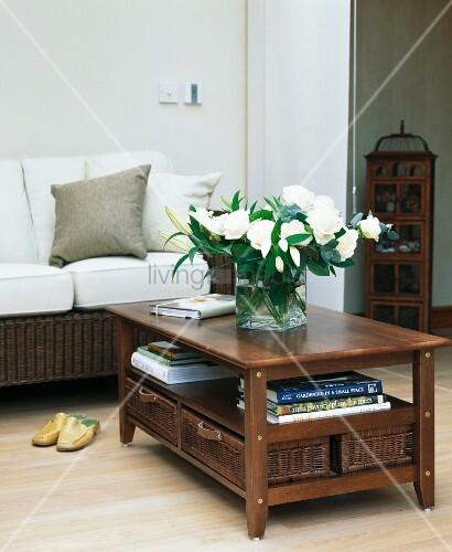 weisse rosen und lilien auf dunklem holztisch vor korbsofa in modernem wohnzimmer mit laminat. Black Bedroom Furniture Sets. Home Design Ideas