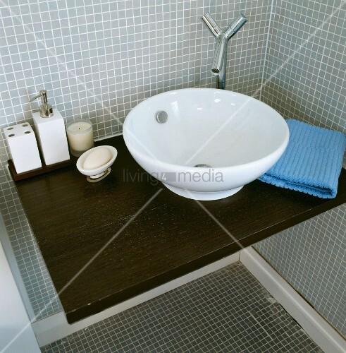 runde waschsch ssel mit designer armatur auf waschtisch in dunklem holz vor hellgrauen. Black Bedroom Furniture Sets. Home Design Ideas