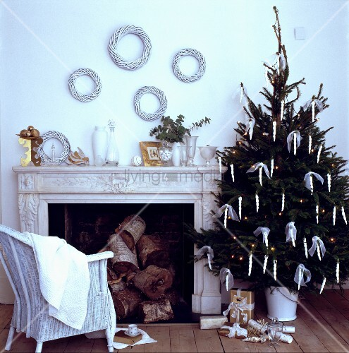 weihnachtsbaum und englischer korbstuhl vor kamin in weissem traditionellem wohnzimmer bild. Black Bedroom Furniture Sets. Home Design Ideas