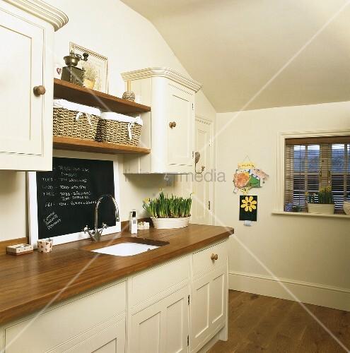 Cremefarbene Küchenzeile mit hölzerner Arbeitsplatte und