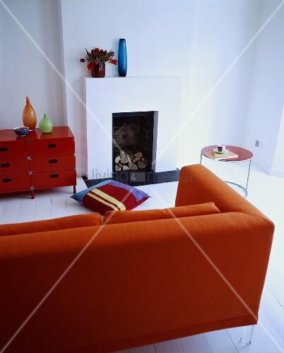 rotes sofa und schr nkchen in einem weissen wohnzimmer mit kamin bild kaufen living4media. Black Bedroom Furniture Sets. Home Design Ideas
