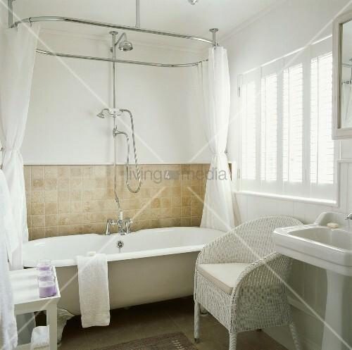 landhaus badezimmer mit weissem englischen korbstuhl neben badewanne mit klauenf ssen und