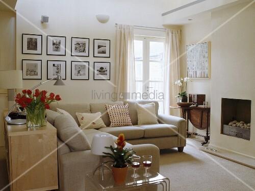 beige sofas und gerahmte schwarzwei fotografien im cremefarbenen zeitgen ssischen wohnzimmer. Black Bedroom Furniture Sets. Home Design Ideas