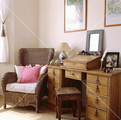 pinke und wei e kissen liegen auf einen korbsessel der neben einen alten kiefer schreibtisch. Black Bedroom Furniture Sets. Home Design Ideas