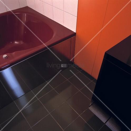 eine dunkelrote badewanne schwarze bodenfliesen und eine. Black Bedroom Furniture Sets. Home Design Ideas