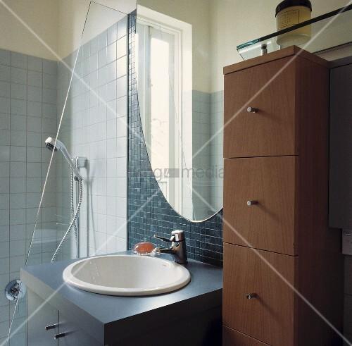 ein rundes waschbecken ist in einem grauen unterschrank eingebracht worden der zwischen eines. Black Bedroom Furniture Sets. Home Design Ideas