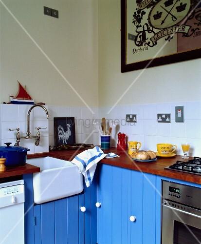 weisses keramiksp lbecken mit altmodischer armatur zwischen strahlend hellblauen einbauschr nken. Black Bedroom Furniture Sets. Home Design Ideas