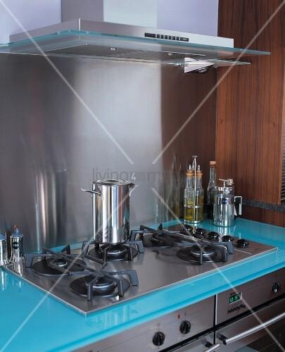 gaskochfeld aus edelstahl mit arbeitsfl che aus blauem glas und passender dunstabzugshaube. Black Bedroom Furniture Sets. Home Design Ideas