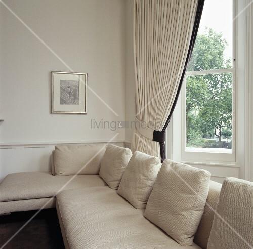 cremefarbenes sofa und gardinen vor dem erkerfenster in einem zeitgen ssischen wohnzimmer bild. Black Bedroom Furniture Sets. Home Design Ideas