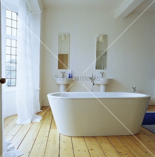 eine frei stehende weisse badewanne in einem badezimmer. Black Bedroom Furniture Sets. Home Design Ideas