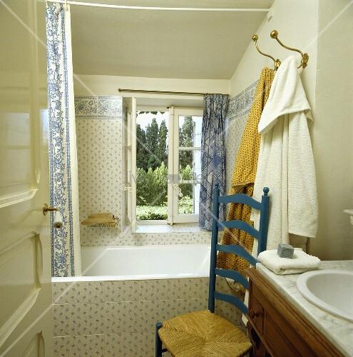 l ndliches badezimmer mit blau weissen fliesen und einem ladderback stuhl bild kaufen. Black Bedroom Furniture Sets. Home Design Ideas