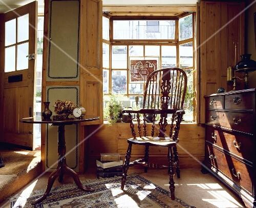 antiker windsor stuhl ein viktorianischer tisch und eine kommode vor dem fenster bild kaufen. Black Bedroom Furniture Sets. Home Design Ideas