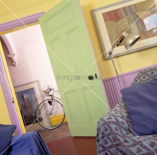 Blick aus einem Wohnzimmer mit gelber Wand und grüner Tür ...