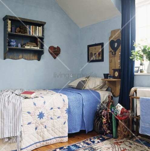 einzelbett mit l ndlicher tagesdecke und blau get nte wand im dachzimmer bild kaufen. Black Bedroom Furniture Sets. Home Design Ideas