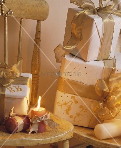 weihnachtsgeschenke mit wei em papier und goldenem band auf rustikalem stuhl mit kerzenlicht. Black Bedroom Furniture Sets. Home Design Ideas