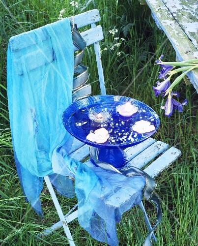 schwimmende kerzen in blauer glasschale auf pastellblauem stuhl bild kaufen living4media. Black Bedroom Furniture Sets. Home Design Ideas