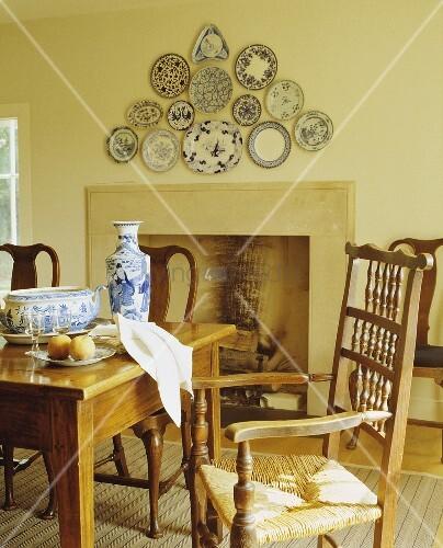 tisch und st hle aus holz vor kamin im l ndlichen gelb get nten esszimmer bild kaufen. Black Bedroom Furniture Sets. Home Design Ideas