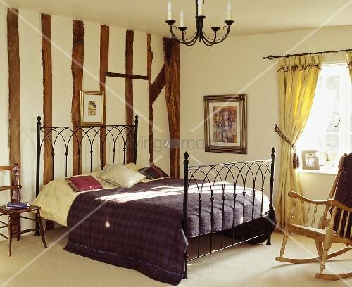 traditionelles schlafzimmer mit bett aus antikem metallgestell vor holzbalkenwand bild kaufen. Black Bedroom Furniture Sets. Home Design Ideas