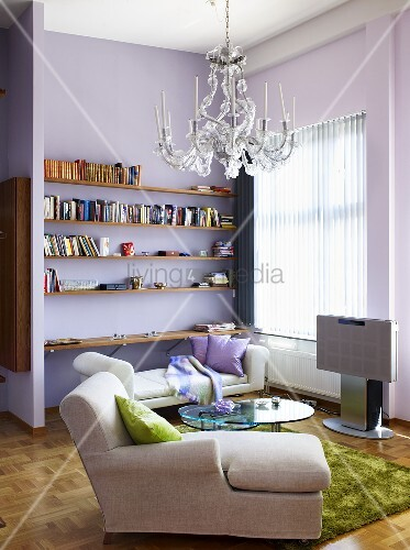 Eine Chaiselounge, ein Tagesbett und Regale in einem Wohnzimmer ...