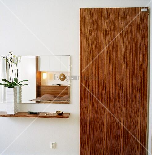 kleine ablage mit orchidee vor einem wandspiegel neben der. Black Bedroom Furniture Sets. Home Design Ideas