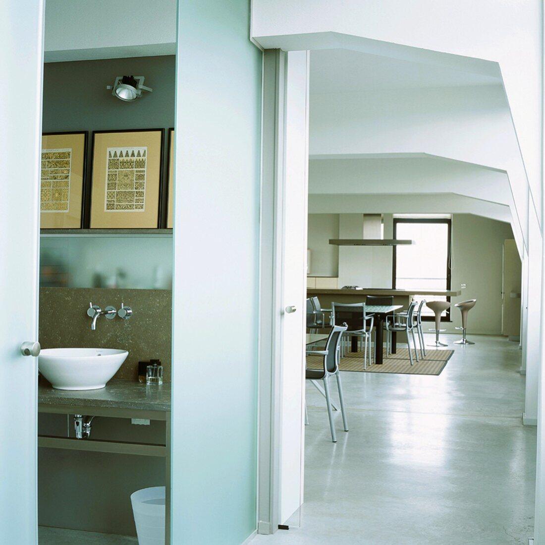 Blick ins Badezimmer und in den Wohnraum eines Lofts mit Rippendecke