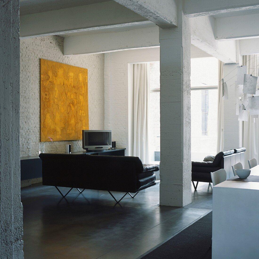 Gelbes Gemälde im modernen Wohnraum eines von Pfeilern getragenen Lofts