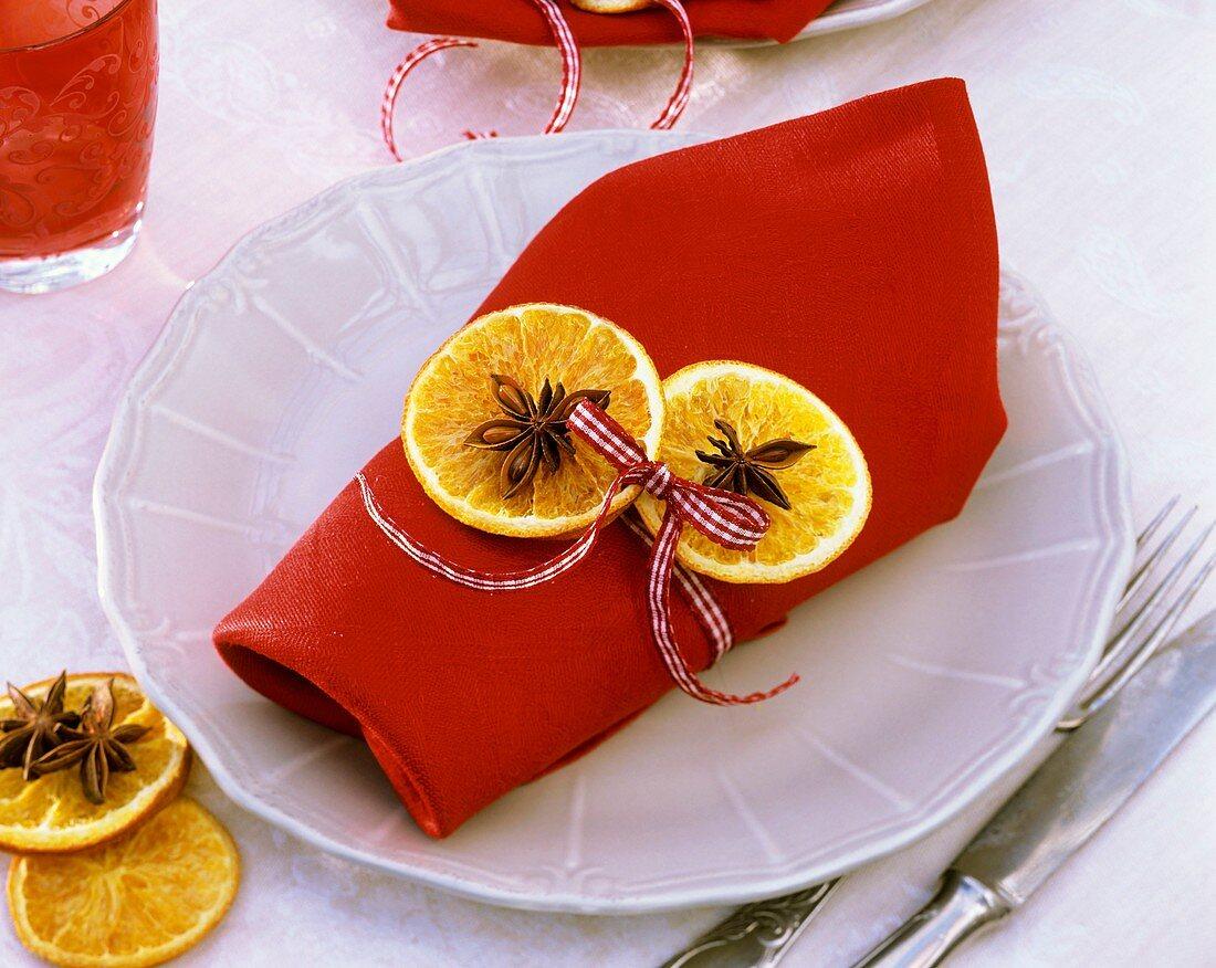 Serviettendekoration mit getrockneten Orangescheiben, Anis