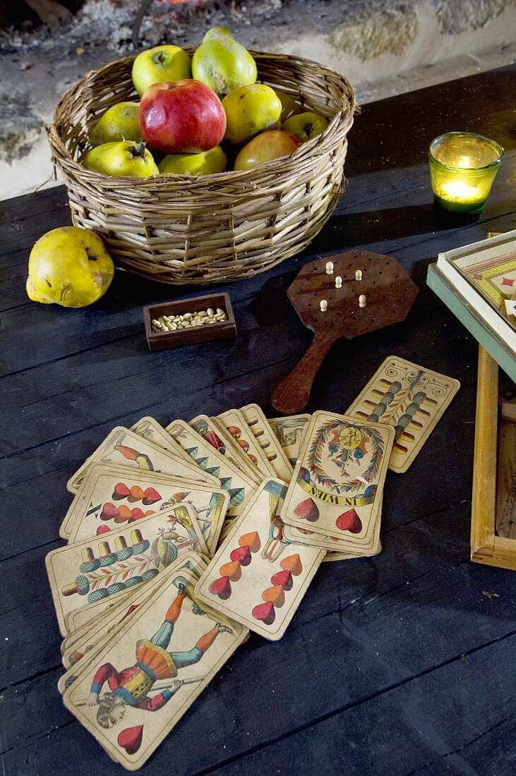 Pack of cards and basket of apples and quinces on a table