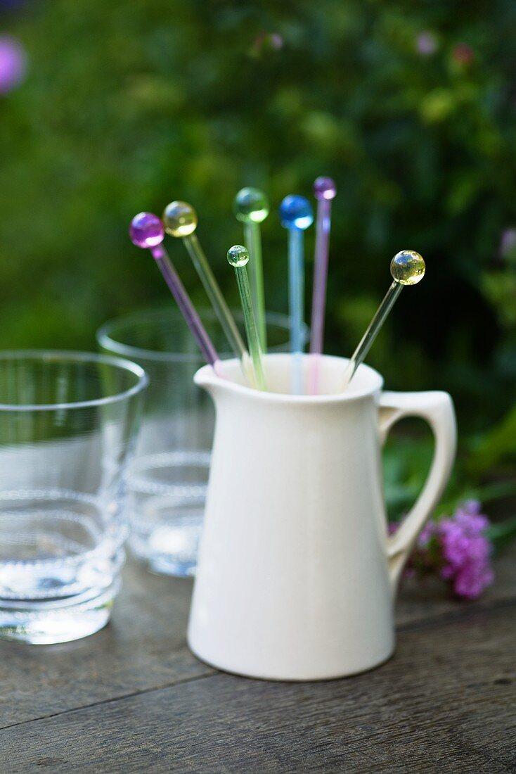 Glass cocktail sticks in ceramic jug