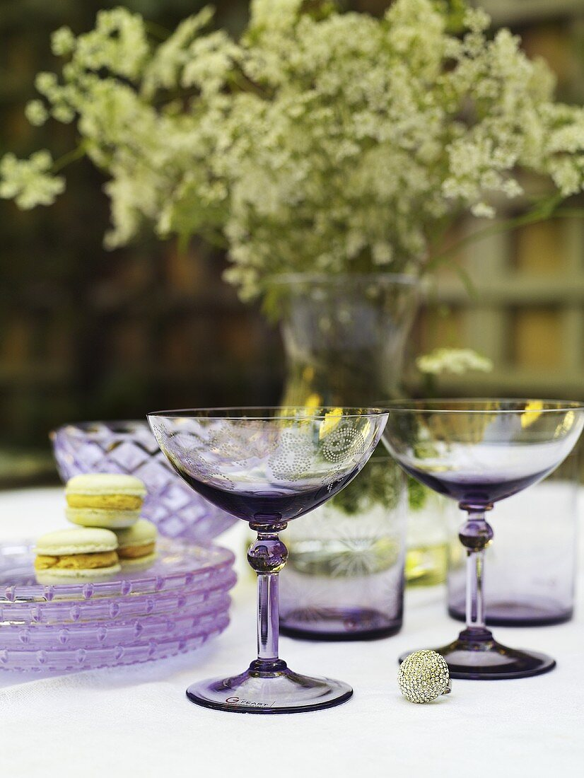 A table decorated for summer with champagne glasses, plates and macaroons