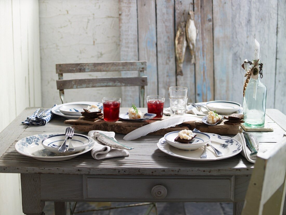 A rustic table laid with Admiral cocktails and black bread with apple lard