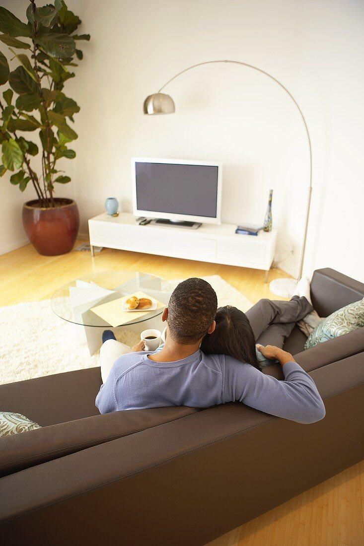 Couple having coffee break on sofa
