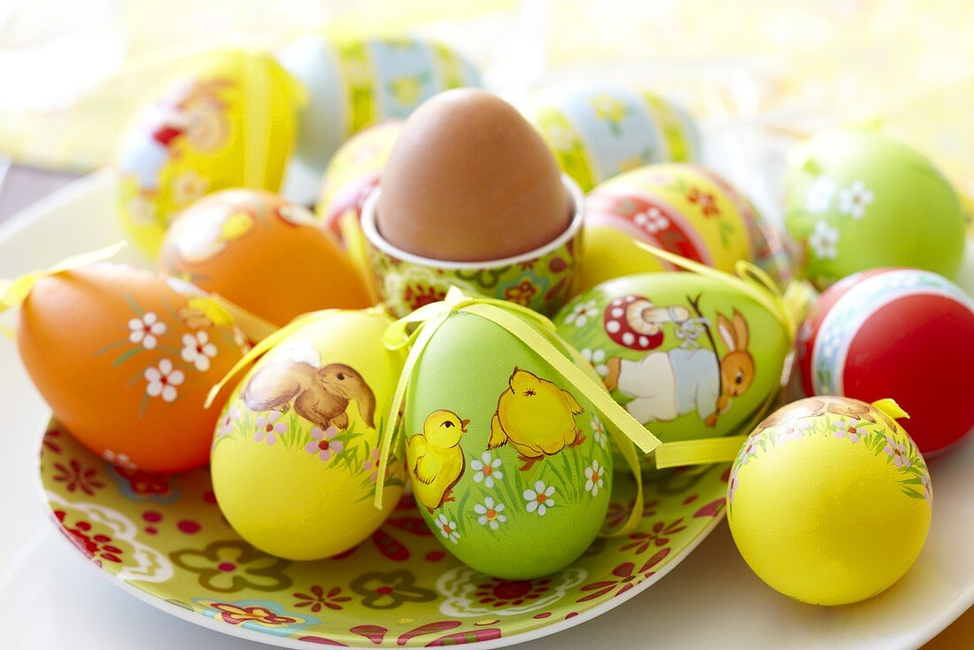 Decorated plastic Easter eggs and a boiled egg in an egg cup