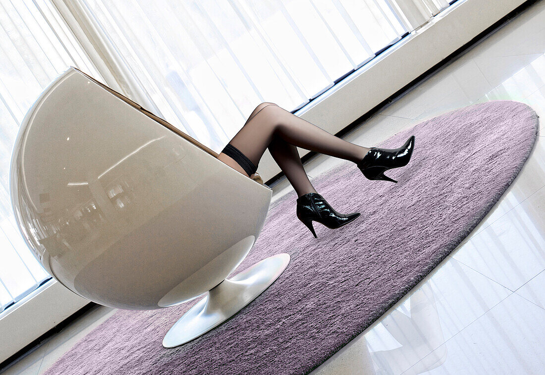 Sexy woman sitting in round armchair